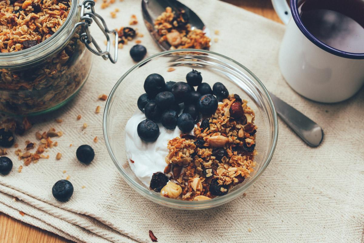 Glasschüssel mit Joghurt und Heidelbeeren enthält zusätzlich ein Knuspermüsli, zubereitet nach einem Granolarezept.