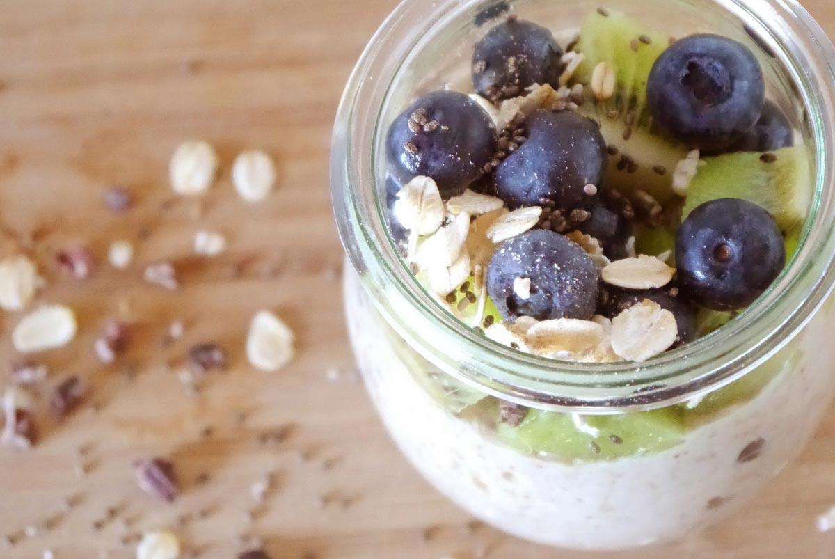 Porridge im Glas mit Heidelbeeren und Kiwi.