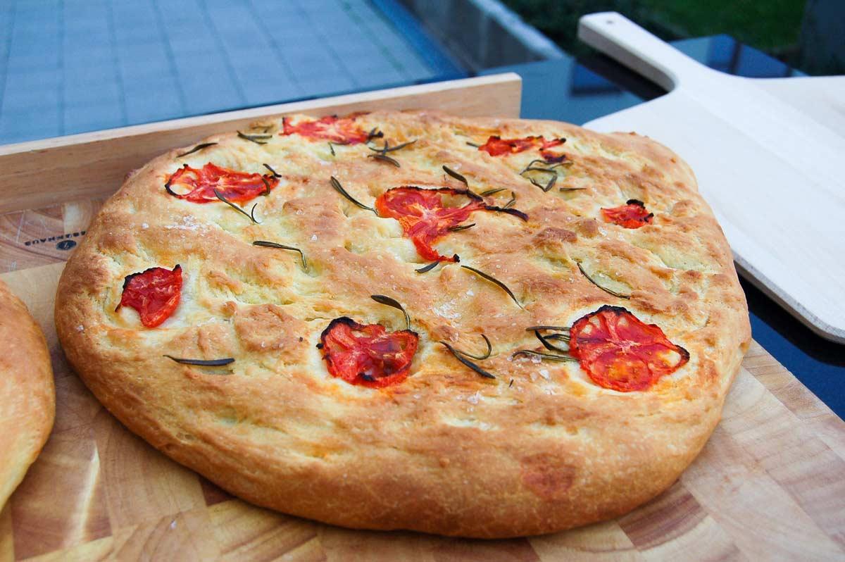 Runde Focaccia mit Tomaten und Rosmarin, die auf einem Holzbrett liegt.