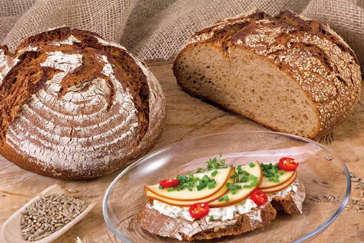 Beim Brot backen mit Emmer entsteht beispielsweise dieses runde Laib Brot, das mit Käse, Chili und Schnittlauch belegt ist.