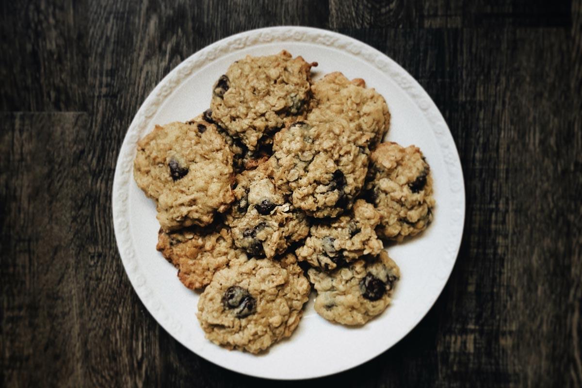 Emmer-Dattel-Kekse auf einem runden Teller, der auf einem dunklen Holztisch steht. Bildquelle: Unsplash