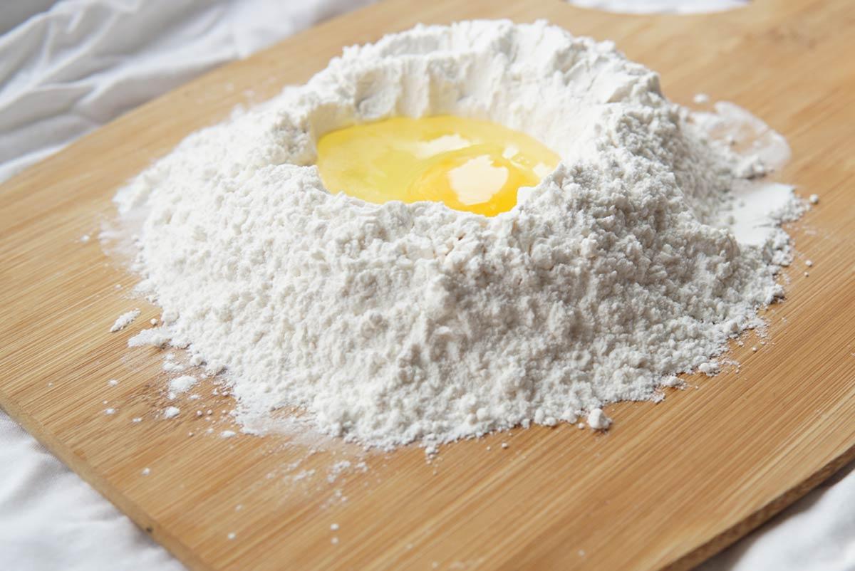 Weizenfreie Ernährung: Mehlhaufen mit Mulde und Ei darin.