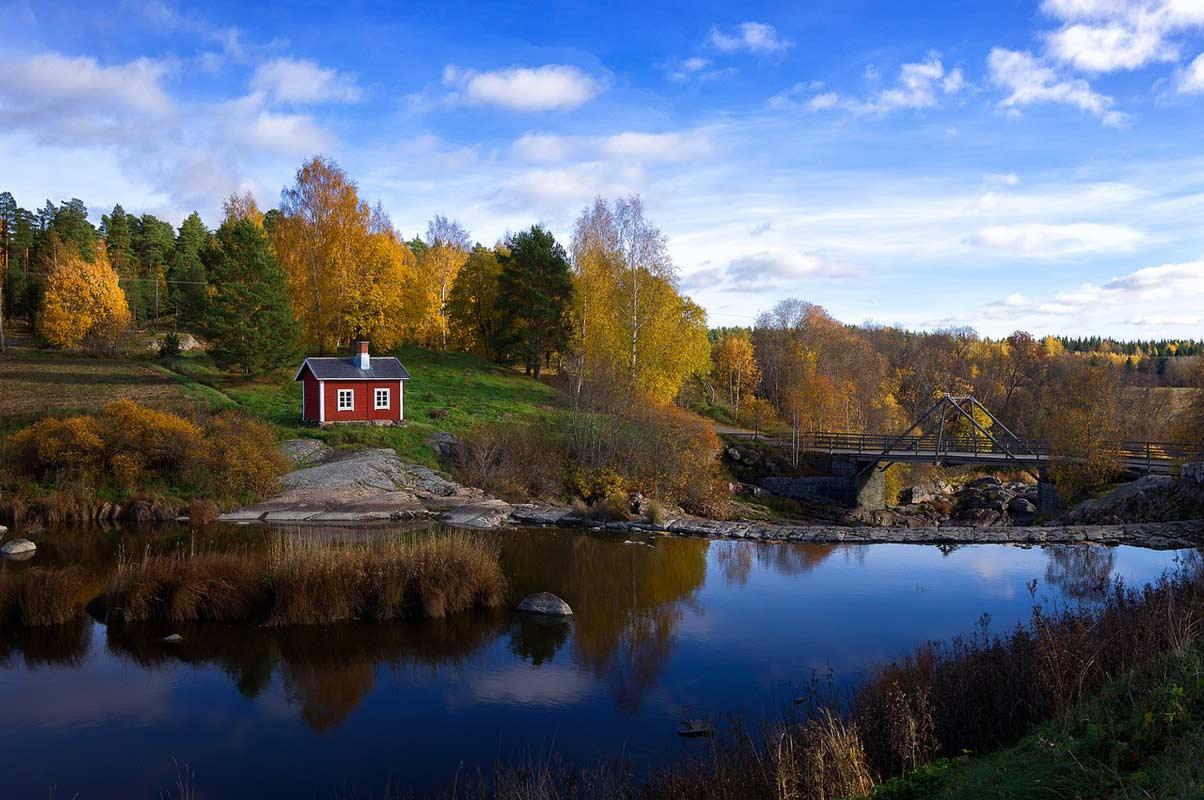 Landschaft mit Fluss, Haus und Brücke, umgeben von Wäldern, in Finnland, wo Emmer als Getreide eine wichtige Rolle spielt.